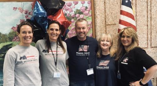staff pose for picture wearing their mission united t-shirts in honor of our veterans