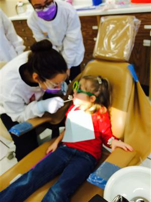 Dental Assisting student counting preschool student's teeth