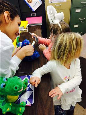 Dental Assisting student shows preschool children how to brush their teeth