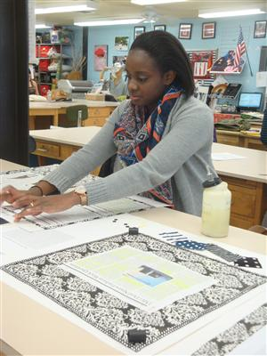 Ms. Sim's student Nylejah is putting finishing touches on her mood board