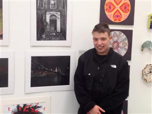 Ms. Grafer's student John poses in front of his exhibit at the Parrish Art Museum